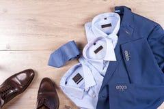 Insieme dei vestiti degli uomini classici - vestito blu, camice, scarpe marroni, cinghia e legame su fondo di legno Fotografia Stock