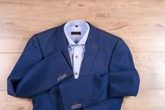 Insieme dei vestiti degli uomini classici - vestito blu, camice, scarpe marroni, cinghia e legame su fondo di legno Immagini Stock