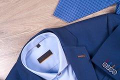 Insieme dei vestiti degli uomini classici - vestito blu, camice, scarpe marroni, cinghia e legame su fondo di legno Immagine Stock