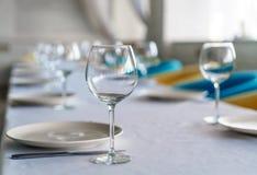 Insieme dei vetri e dei piatti di vino vuoti puliti su un tavolo da pranzo con le sedie variopinte su un fondo pastello interno d Fotografia Stock