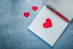 Insieme del blocco note pulito dei cuori della penna rossa del biro su fondo metallico Fotografia Stock