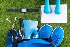 Insieme del blu delle cose per il cardio allenamento, su un prato inglese verde con un orologio astuto Immagini Stock Libere da Diritti