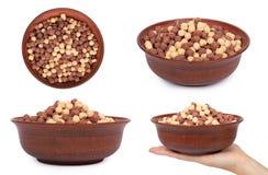 insieme del cereale da prima colazione del cioccolato differente in ciotola con la mano, isolato sulle palle marroni e bianche bi Fotografie Stock Libere da Diritti