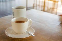 Insieme del freno del caffè, caffè espresso delle tazze di caffè con i cucchiai sul tabl Immagini Stock