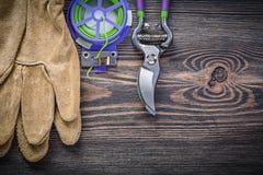 Insieme del legame di torsione molle dei guanti di sicurezza delle cesoie sul bordo di legno GA Fotografia Stock Libera da Diritti