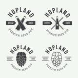 Insieme del logos d'annata del pub e della birra, etichette ed emblemi con le bottiglie, il luppolo ed il grano illustrazione di stock