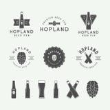 Insieme del logos d'annata del pub e della birra, etichette ed emblemi con le bottiglie, il luppolo ed il grano Fotografia Stock