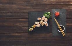 Insieme del maki e dei rotoli dei sushi a legno rustico nero Immagine Stock