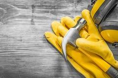 Insieme del martello da carpentiere degli abiti da lavoro di sicurezza sulla costruzione del bordo di legno Fotografia Stock Libera da Diritti