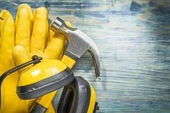 Insieme del martello da carpentiere protettivo degli abiti da lavoro sulla costruzione del bordo di legno Immagine Stock