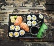 Insieme del menu dei sushi in scatola nera di trasporto su fondo di legno scuro, vista superiore fotografia stock