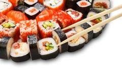 Insieme del primo piano dei sushi, di maki e dei rotoli con i bastoncini Immagini Stock