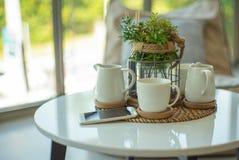 Insieme del primo piano della tazza e della brocca ceramiche bianche di tè e di caffè con il telefono di mobil fotografia stock libera da diritti