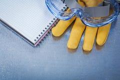 Insieme del quaderno dei guanti di cuoio dei vetri di protezione sulle sedere metalliche Fotografia Stock Libera da Diritti