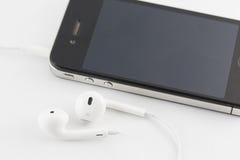 Insieme dell'attrezzatura bianca di Smartphone e del trasduttore auricolare isolato sulle sedere bianche Fotografia Stock