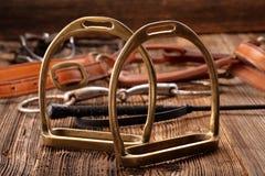 Insieme dell'attrezzatura del cavallo su fondo di legno Fotografie Stock