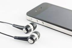 Insieme dell'attrezzatura nera di Smartphone e del trasduttore auricolare isolato sulle sedere bianche Fotografia Stock Libera da Diritti