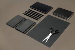 Insieme della cancelleria nera su un fondo grigio, disposizione piana dell'ufficio Fotografie Stock