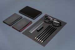 Insieme della cancelleria nera su un fondo grigio, disposizione piana dell'ufficio Fotografia Stock