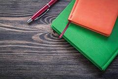 Insieme della penna di brio dei blocchi note sul concetto d'annata dell'ufficio del bordo di legno Fotografia Stock