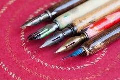 Insieme della penna stilografica Accessori della scrittura di calligrafia, penne variopinte d'annata dell'artista, fondo di carta Immagine Stock