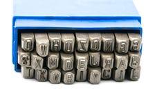 Insieme della perforazione di alfabeto del bollo del metallo in scatola di plastica blu Fotografia Stock Libera da Diritti