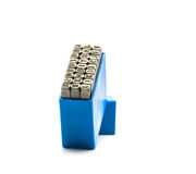 Insieme della perforazione di alfabeto del bollo del metallo in scatola di plastica blu Fotografia Stock