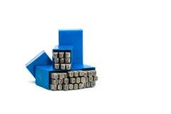 Insieme della perforazione di alfabeto e di numero del bollo del metallo in scatola di plastica blu isolata su fondo bianco Fotografie Stock Libere da Diritti