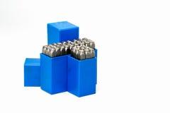 Insieme della perforazione di alfabeto e di numero del bollo del metallo in scatola di plastica blu isolata su fondo bianco Fotografie Stock