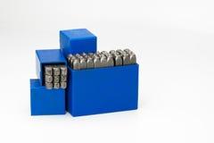 Insieme della perforazione di alfabeto e di numero del bollo del metallo in scatola di plastica blu isolata su fondo bianco Fotografia Stock