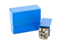 Insieme della perforazione di numero del bollo del metallo in scatola di plastica blu Fotografie Stock Libere da Diritti