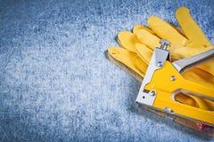 Insieme della pistola della cucitrice meccanica dei guanti di sicurezza sul construc metallico del fondo Fotografie Stock