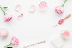 insieme della stazione termale con i fiori ed il cosmetico rosa per il corpo sul modello bianco di vista superiore del fondo dell Fotografie Stock