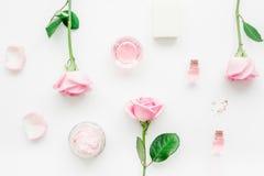 Insieme della stazione termale con i fiori ed il cosmetico rosa per il corpo sulla vista superiore del fondo bianco dello scritto Fotografia Stock Libera da Diritti