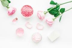 Insieme della stazione termale con i fiori ed il cosmetico rosa per il corpo sulla vista superiore del fondo bianco dello scritto Fotografie Stock Libere da Diritti