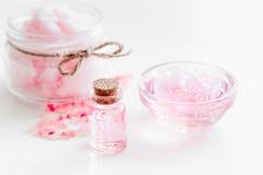 Insieme della stazione termale con i fiori rosa estratto e cosmetico per il corpo sul fondo bianco dello scrittorio Immagine Stock