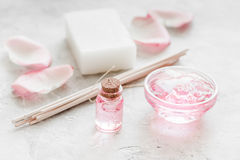 Insieme della stazione termale con i fiori rosa estratto e cosmetico per il corpo sul fondo bianco dello scrittorio Fotografia Stock