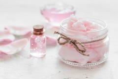 Insieme della stazione termale con i fiori rosa estratto e cosmetico per il corpo sul fondo bianco dello scrittorio Immagine Stock Libera da Diritti