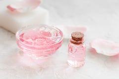 Insieme della stazione termale con i fiori rosa estratto e cosmetico per il corpo sul fondo bianco dello scrittorio Immagini Stock