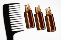 Insieme delle ampolle con un'ombra del pettine dei capelli Immagine Stock