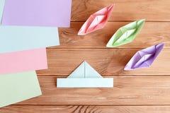 Insieme delle barche di origami e dei fogli quadrati di carta colorata su una tavola di legno Fotografie Stock