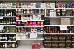 Insieme delle bottiglie dell'alcool su uno scaffale al supermercato Immagini Stock