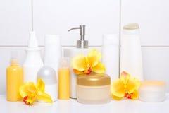 Insieme delle bottiglie e dei rifornimenti cosmetici bianchi di igiene con la f arancio Fotografia Stock Libera da Diritti