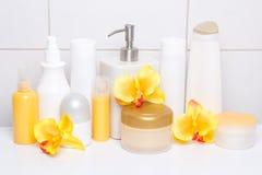 Insieme delle bottiglie e dei rifornimenti cosmetici bianchi di igiene con la o arancio Fotografia Stock