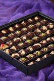 Insieme delle caramelle di cioccolato fatte a mano di lusso con i dadi in contenitore di regalo Immagine Stock