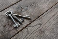 Insieme delle chiavi d'annata arrugginite su legno invecchiato Immagine Stock Libera da Diritti
