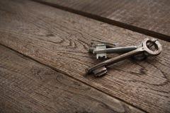 Insieme delle chiavi d'annata arrugginite su legno invecchiato Fotografia Stock