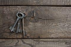 Insieme delle chiavi d'annata arrugginite su legno invecchiato Fotografie Stock Libere da Diritti