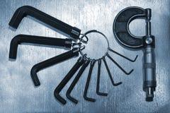 Insieme delle chiavi di Allen della sfortuna e micrometro della vite su fondo d'acciaio Immagine Stock