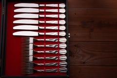 Insieme delle forcelle e dei coltelli in un caso Immagini Stock
